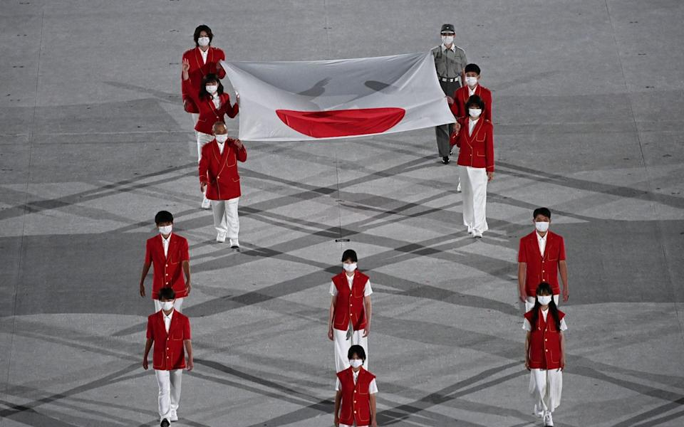 Athletes carry the Japanese national flag during the opening ceremony of the Tokyo 2020 Olympic Games - LIONEL BONAVENTURE/AFP via Getty Images