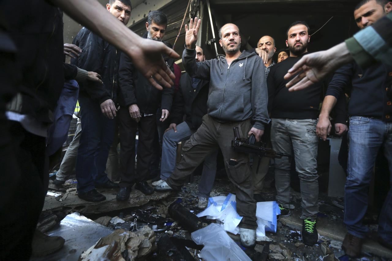 Civilians and Hezbollah members stand at the site of an explosion in the Haret Hreik area, in the southern suburbs of the Lebanese capital Beirut January 21, 2014. A suicide bomber killed four people on Tuesday in the residential district of southern Beirut known for its support of the powerful Shi'ite Muslim military and political movement Hezbollah, security sources said. REUTERS/Hasan Shaaban (LEBANON - Tags: POLITICS CIVIL UNREST)