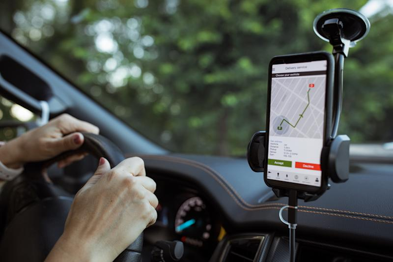 Picture of a mobile phone, providing navigation for the driver on a cradle, which is legal for unrestricted drivers.