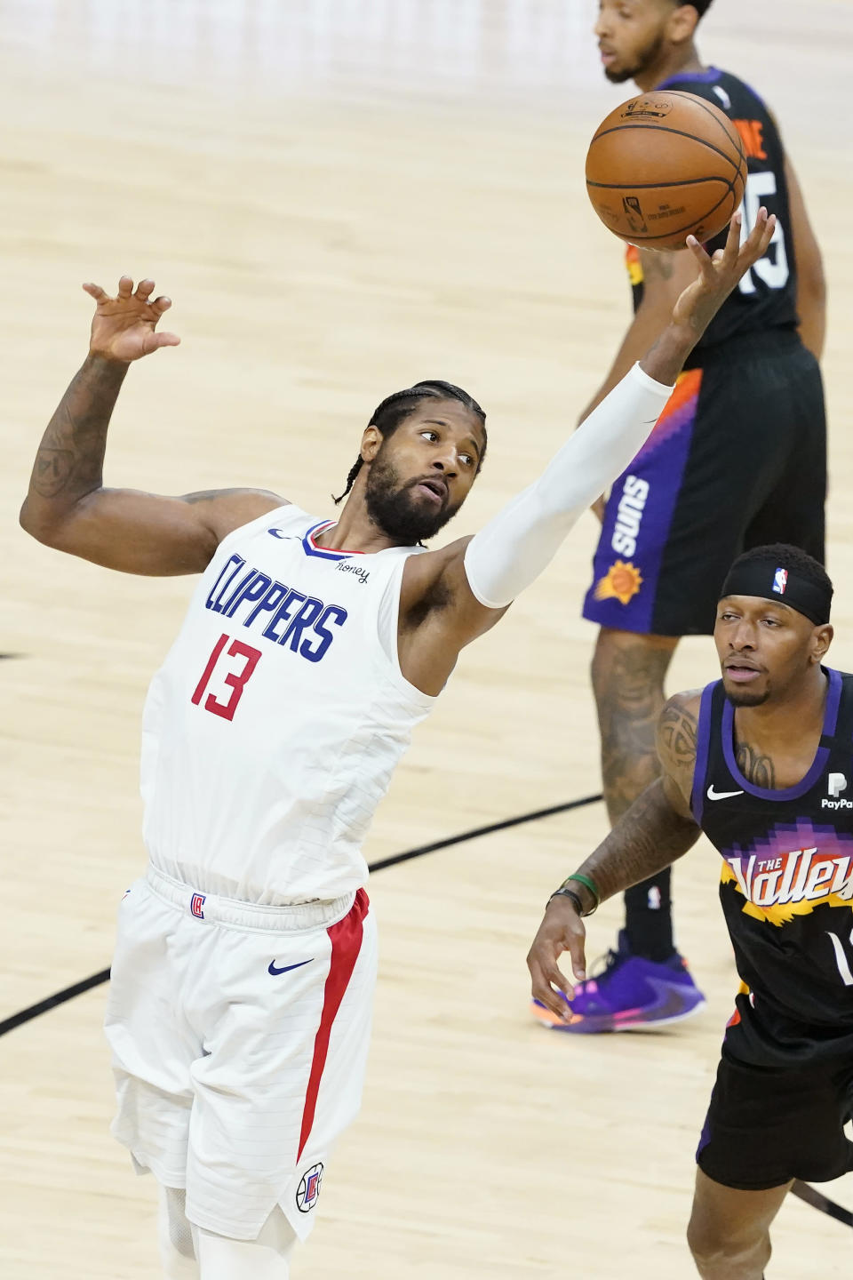 Los Angeles Clippers guard Paul George (13) is defended by Phoenix Suns forward Torrey Craig during the second half of Game 2 of the NBA basketball Western Conference Finals, Tuesday, June 22, 2021, in Phoenix. (AP Photo/Matt York)