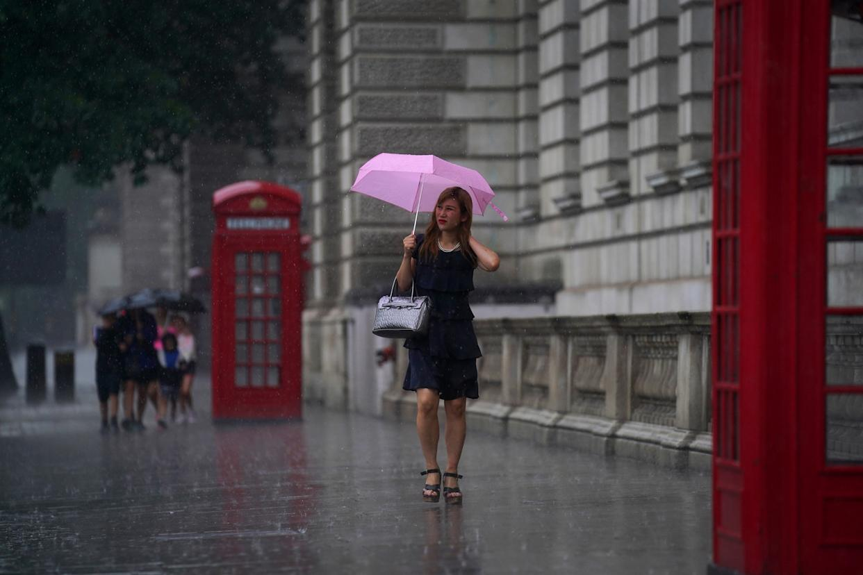 A woman walks through Parliament Square as heavy rain sweeps through central London. Thunderstorms bringing lightning and torrential rain to the south are set to continue until Monday, forecasters have said. Picture date: Sunday July 25, 2021.