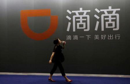 FILE PHOTO - A woman walks past Didi Chuxing's booth at the GMIC in Beijing