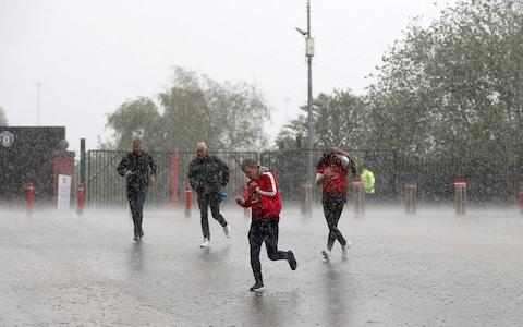 Fans race to the game in the rain - Credit: PA