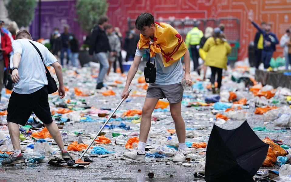 Scotland fans clean up litter in Leicester Square, London, ahead of the UEFA Euro 2020 - Kirsty O'Connor/PA