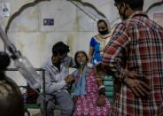 FILE PHOTO: A woman with a breathing problem receives oxygen support for free at a Gurudwara, in Ghaziabad