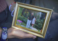 """Noreen Wasti shows a framed family photo of herself as a child with her father, Thursday June 24, 2021, in Brooklyn, N.Y. Wasti lost her father Salman Wasti, 76, a retired biology professor from Glocester, R.I., the day after Christmas last year to COVID-19 and is having a hard time coping with his death. """"This has been the first time I've lost someone so dear to me, so I never had a map for grief nor really understood the magnitude."""" (AP Photo/Bebeto Matthews)"""