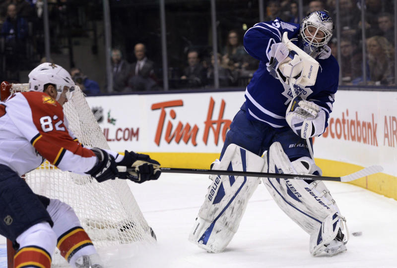 Toronto Maple Leafs goalie James Reimer plays the puck from behind his net as Florida Panthers' Tomas Kopecky skates in during first period NHL action in Toronto on Tuesday, Dec. 17, 2013. (AP Photo/The Canadian Press, Frank Gunn)