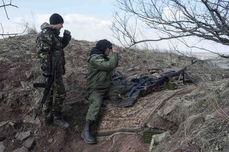 Pro-Russian rebels observe the area at a front line outside the village of Molochnoye, north-east from Donetsk