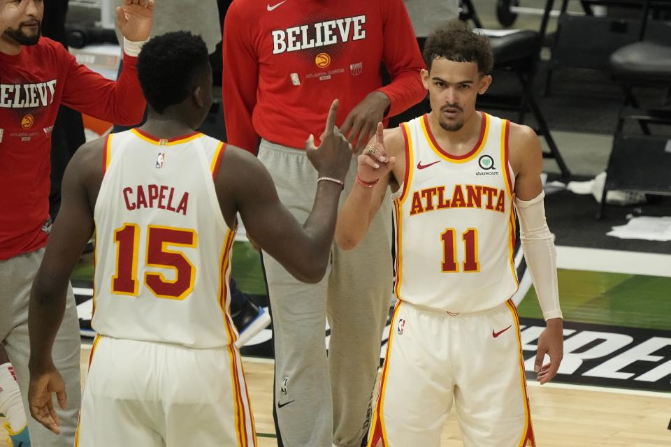Atlanta Hawks' Trae Young and Clint Capela celebrate after Game 1 of the NBA Eastern Conference basketball finals game against the Milwaukee Bucks Wednesday, June 23, 2021, in Milwaukee. The Hawks won 116-113 to take a 1-0 lead in the series. (AP Photo/Morry Gash)