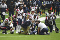 New England Patriots players kneel as teammate Rex Burkhead is attended to after he was injured during a run against the Houston Texans during the second half of an NFL football game, Sunday, Nov. 22, 2020, in Houston. (AP Photo/Eric Christian Smith)