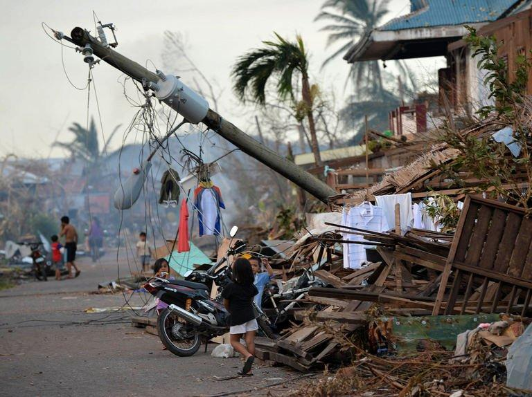 Children walk near a toppled electricity post in Boston town, Davao Oriental province on December 10, 2012