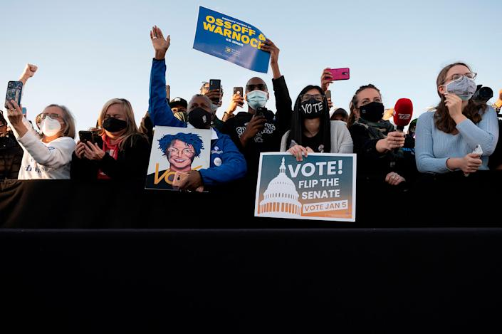 """Supporters of democratic candidates for Senate Jon Ossoff and Raphael Warnock listen to President-elect Joe Biden speak during a rally in Atlanta, on Jan. 4, 2021.<span class=""""copyright"""">Jim Watson—AFP/Getty Images</span>"""