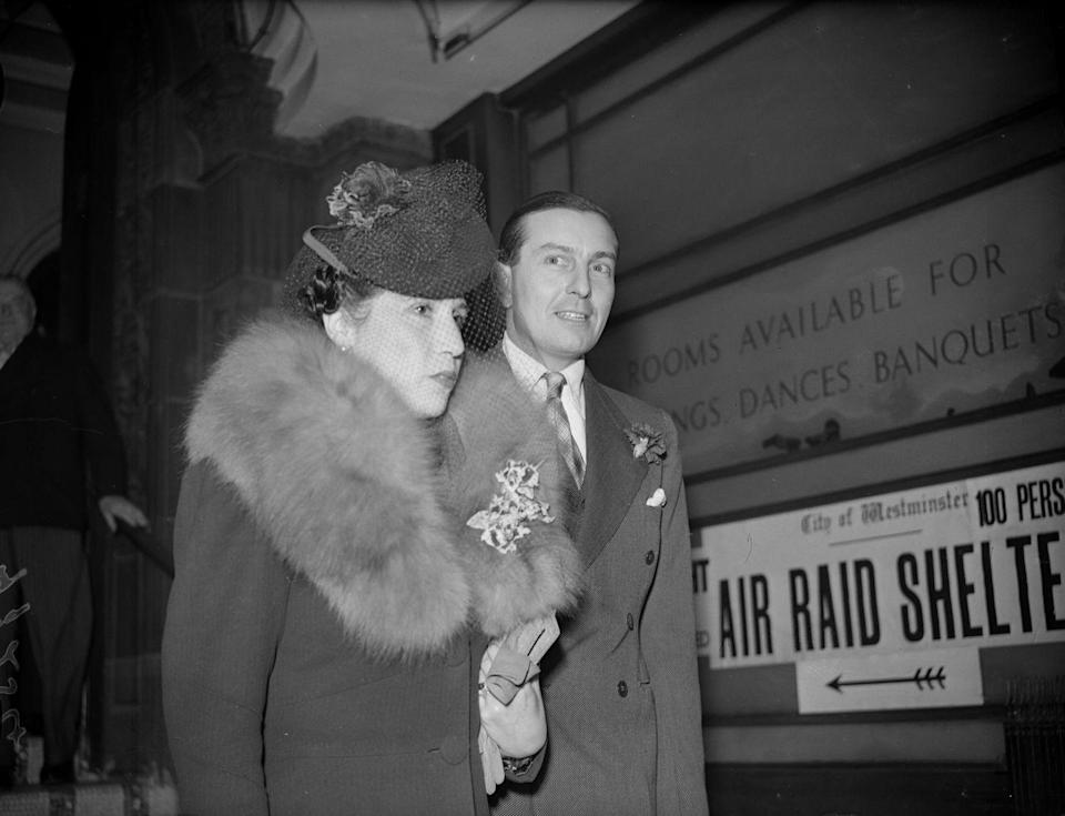 <p>With the start of World War II, bridal fashions became more modest. Weddings were often planned in a few days, to accommodate men who were on short-notice leave. Pictured above, professional golfer Henry Cotton and his bride, Mrs. M. I. Moss, on their wedding day. A sign in the background points to an air-raid shelter. </p>