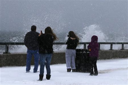 Onlookers look at waves crashing against the seawall around high tide during a winter nor'easter snowstorm in Lynn, Massachusetts January 2, 2014. REUTERS/Brian Snyder