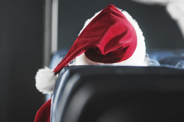 Man wearing santa costume sitting on aeroplane seat, rear view