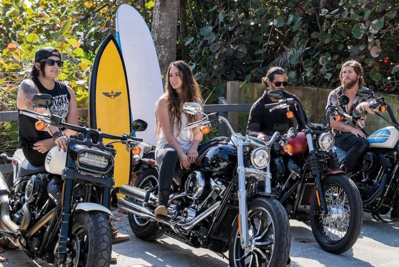 Four riders on Harley-Davidson motorcycles in front of surfboards