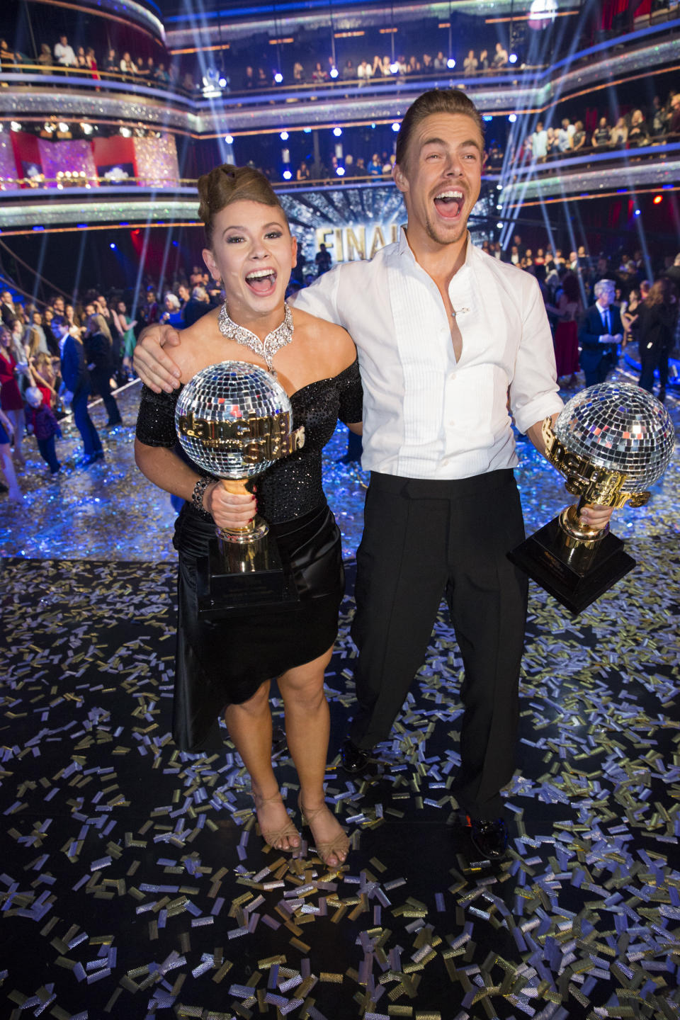 Bindi Irwin n black off the shoulder dress and Derek Hough holding the Dancing With The Stars trophies during the two-hour season finale of Dancing with the Stars