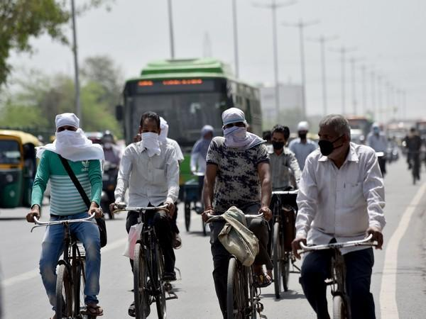 People cover their faces and heads to protect themselves from scorching heat in Delhi. (Photo/ANI)