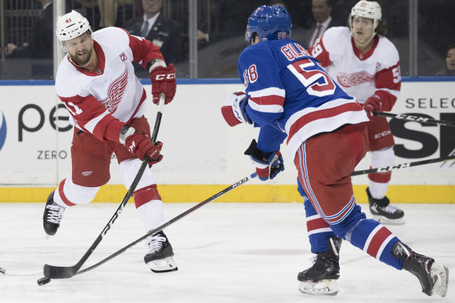 Detroit Red Wings center Luke Glendening shoots the puck around New York Rangers defenseman John Gilmour (58) during the first period of an NHL hockey game, Tuesday, March 19, 2019, at Madison Square Garden in New York. (AP Photo/Mary Altaffer)