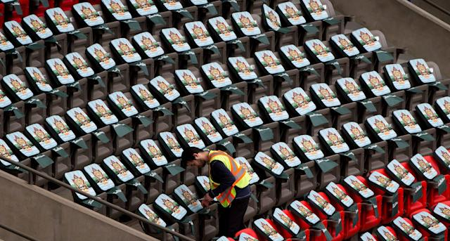 A worker places cushions on seats as B.C. Place stadium is prepared for the NHL Heritage Classic hockey game in Vancouver, British Columbia, on Wednesday, Feb. 26, 2014. The Vancouver Canucks and the Ottawa Senators are scheduled to play on Sunday at the stadium. (AP Photo/The Canadian Press, Darryl Dyck)