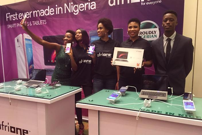 """The AfriOne booth at a telecommunications industry conference in Lagos. During the event's opening session, AfriOne presenters argued for the importance of the company's Lagos assembly line. """"It's made for us, made in Nigeria, made for Africans, made for the world,"""" one of them exclaimed, as puffs of smoke revealed a three-foot mock-up of the company's Champion smartphone. """"It's the first of its kind in Africa. Imagine that! No more importation."""" (Photo: Armin Rosen for Yahoo News)"""