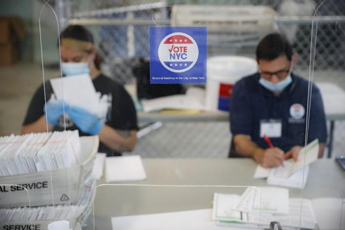 "Workers wear personal protective equipment as they check ballots July 22 at an elections facility in New York. <span class=""copyright"">(John Minchillo / Associated Press)</span>"