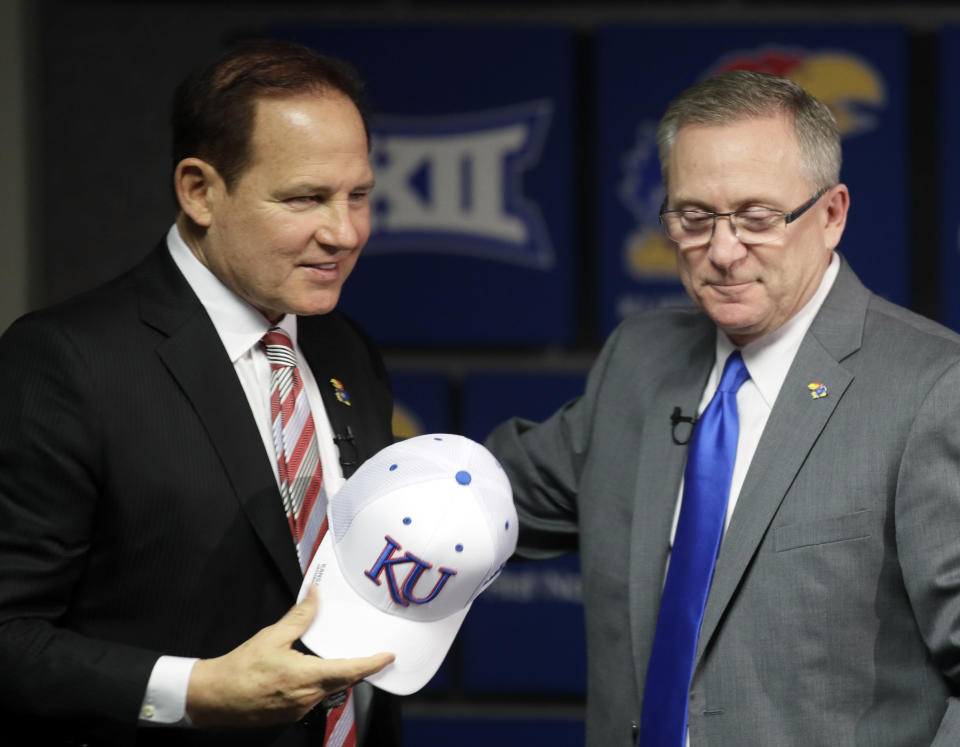 FILE - In this Nov. 18, 2018, file photo, Les Miles, left, is introduced as Kansas football coach by athletic director Jeff Long, right, during a news conference in Lawrence, Kan. Kansas has fired athletic director Jeff Long less than two days after mutually parting with Les Miles amid sexual misconduct allegations dating to the football coachs time at LSU, a person familiar with the decision told The Associated Press on Wednesday, March 10, 2021. (AP Photo/Orlin Wagner, File)