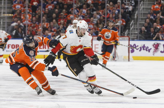 Calgary Flames' Mark Jankowski (77) is chased by Edmonton Oilers' Darnell Nurse (25) during the third period of an NHL hockey game in Edmonton, Alberta, Saturday, Jan. 19, 2019. (Jason Franson/The Canadian Press via AP)
