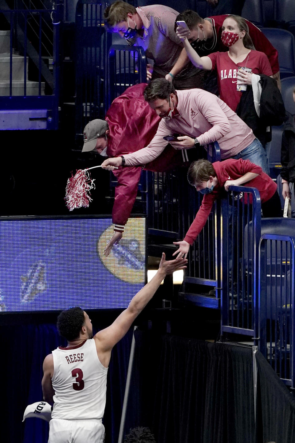 Alabama's Alex Reese (3) jumps up to slap hands with fans as he leaves the court after Alabama beat Tennessee in an NCAA college basketball game in the Southeastern Conference Tournament Saturday, March 13, 2021, in Nashville, Tenn. (AP Photo/Mark Humphrey)