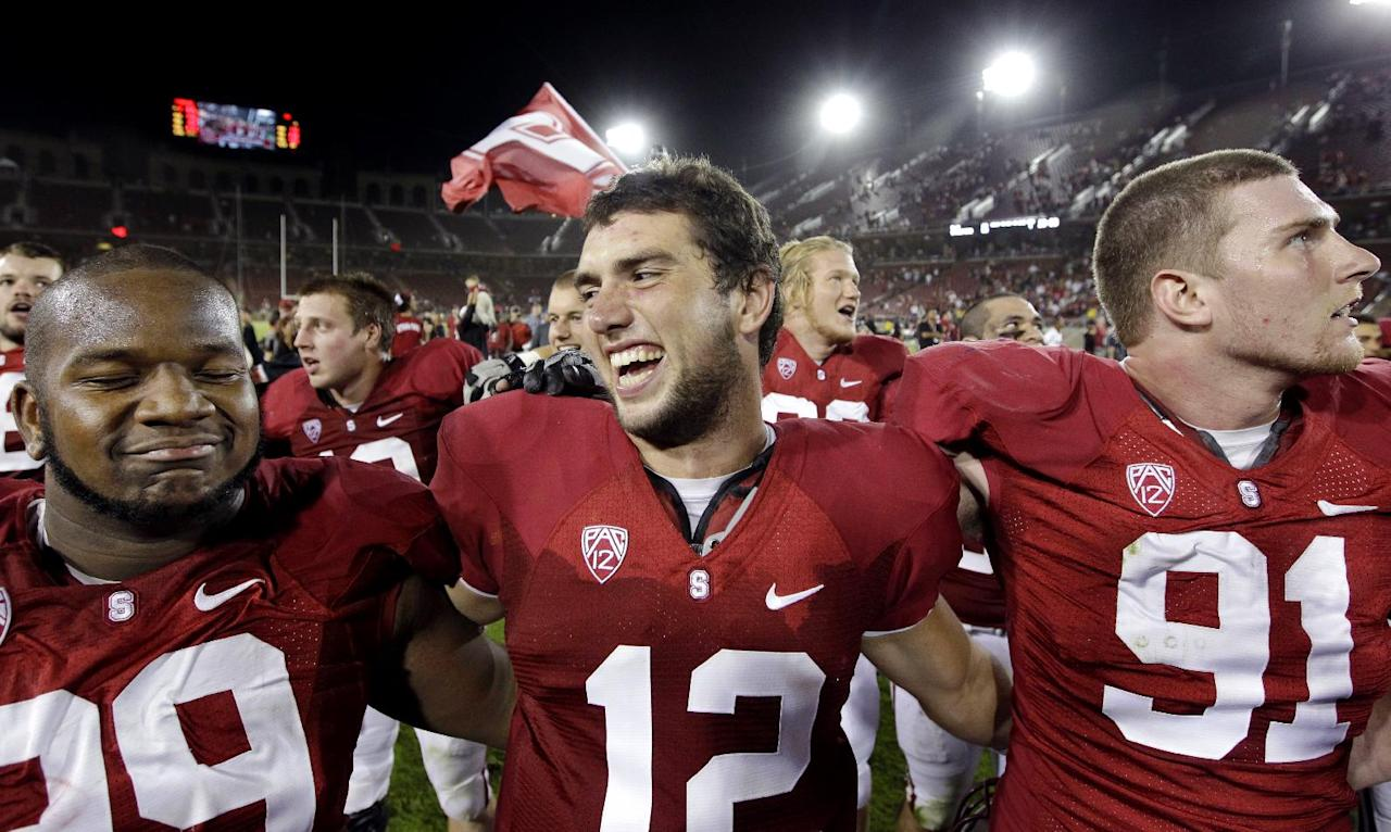 FILE - In this Oct. 22, 2011 file photo, Stanford quarterback Andrew Luck (12) celebrates with defensive tackle Terrence Stephens (99) and defensive end Henry Anderson (91) after an NCAA college football game against Washington in Stanford, Calif. Luck has won the Johnny Unitas Golden Arm Award, presented annually to the nation's top quarterback who best exemplifies character and scholastic and athletic achievement. (AP Photo/Paul Sakuma, file)