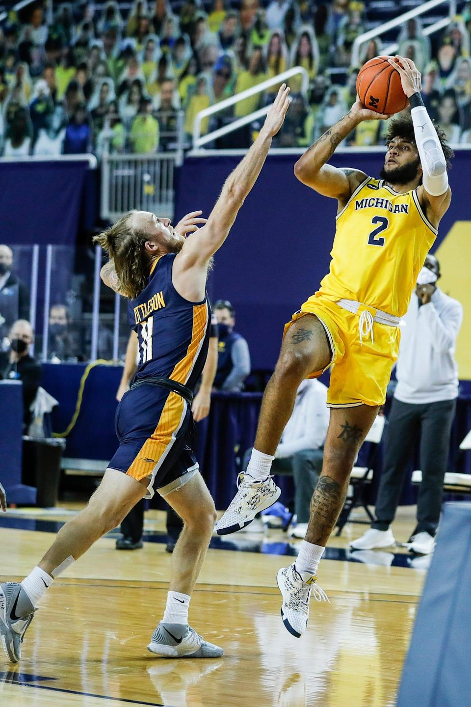 Michigan forward Isaiah Livers makes a jump shot against Toledo guard Spencer Littleson during the first half at Crisler Center in Ann Arbor, Wednesday, Dec. 9, 2020.