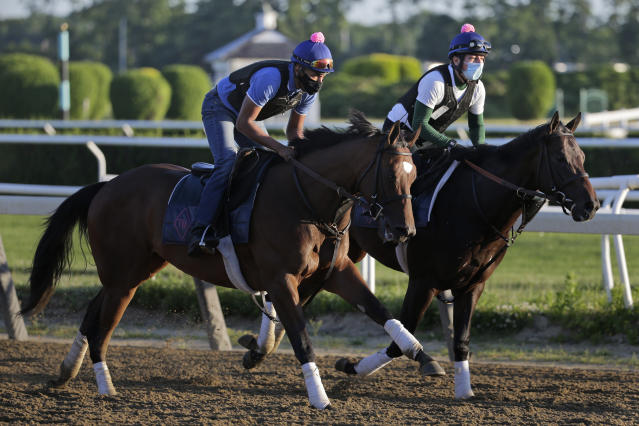 Riders wearing masks workout with horses at Belmont Park in Elmont, N.Y., Wednesday, June 17, 2020. The 152nd running of the Belmont Stakes is scheduled to be run on Saturday. (AP Photo/Seth Wenig)