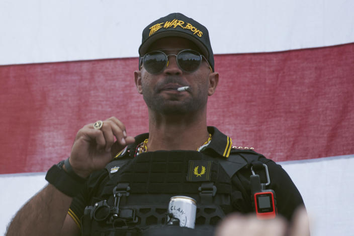 """FILE - In this Sept. 26, 2020, file photo, Proud Boys leader Henry """"Enrique"""" Tarrio wears a hat that says The War Boys during a rally in Portland, Ore. Police in the nation's capital on Jan. 4, 2021, arrested the leader of the Proud Boys, who is accused of burning a Black Lives Matter banner that was torn down from a historic Black church in downtown Washington in December 2020. (AP Photo/Allison Dinner, File)"""
