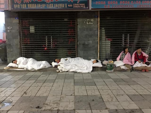 <p>Tourists sleep on a street after an earthquake in Jiuzhaigou county, Ngawa prefecture, Sichuan province, China, Aug. 9, 2017. (Photo: Stringer/Reuters) </p>