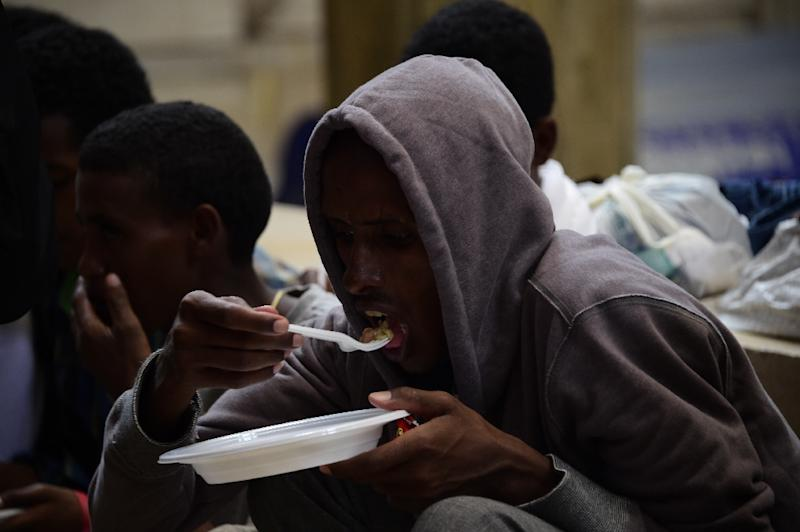 Migrants from Eritrea eat a meal they received from aid workers at the Milan train station on June 11, 2015