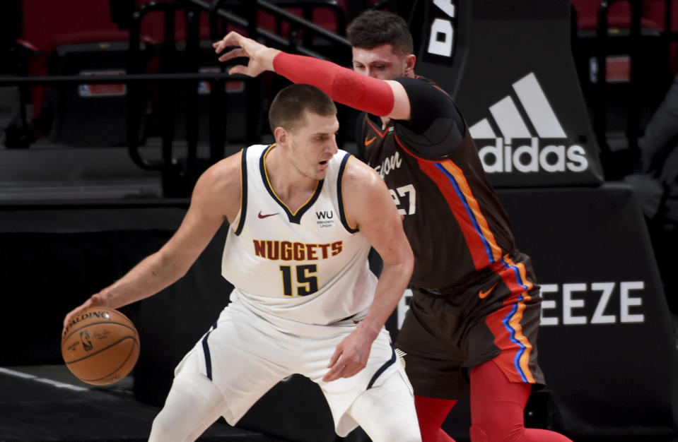 Denver Nuggets center Nikola Jokic, left dribbles the ball on Portland Trail Blazers center Jusuf Nurkic, right, during the first half of an NBA basketball game in Portland, Ore., Sunday, May 16, 2021. (AP Photo/Steve Dykes)