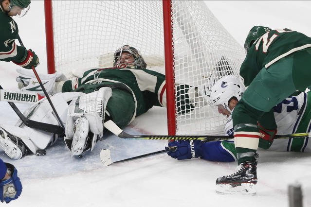 Minnesota Wild's Alex Stalock falls flat on his back as he stops a shot attempt from Vancouver Canucks' Bo Horvat, lower right, during the first period of an NHL hockey game Thursday, Feb. 6, 2020, in St. Paul, Minn. (AP Photo/Jim Mone)