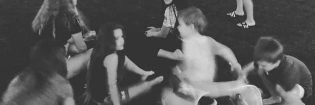 Black and white image of kids dancing, one uses a walker