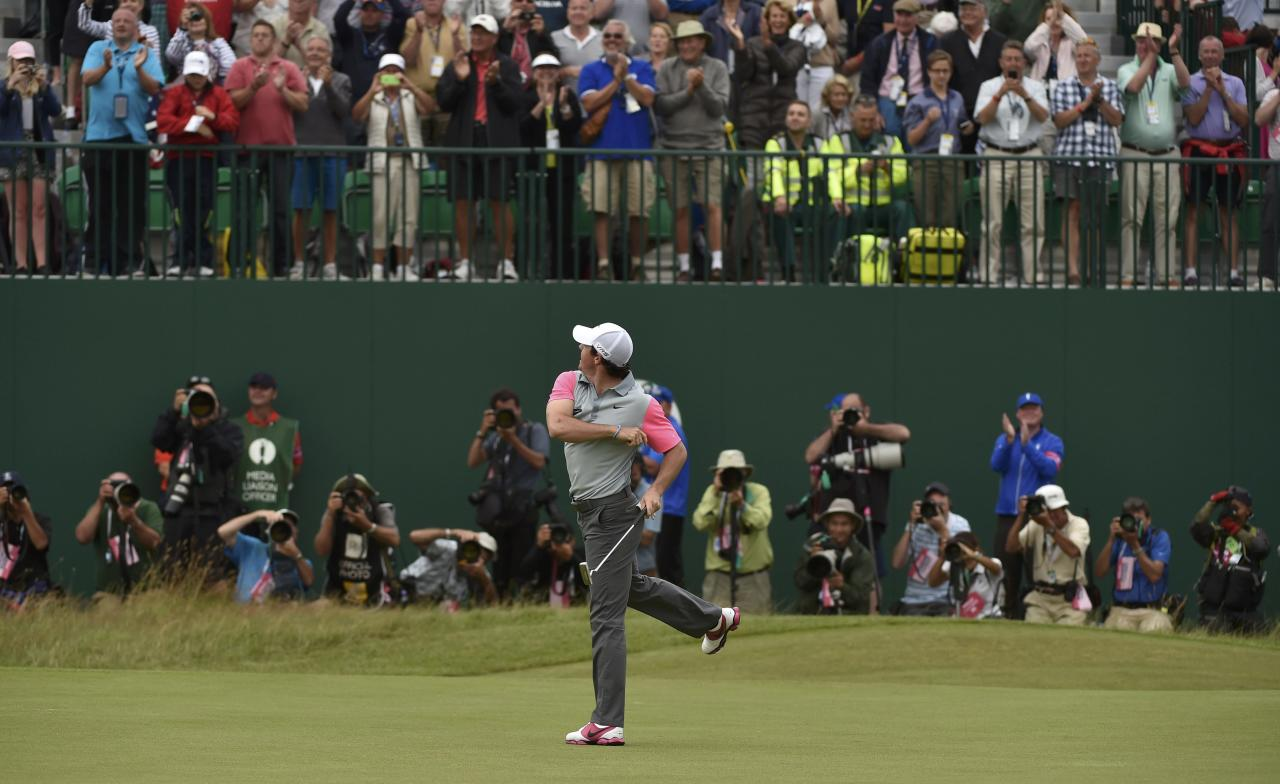 Rory McIlroy of Northern Ireland throws his ball to spectators as he celebrates on the 18th green after winning the British Open Championship at the Royal Liverpool Golf Club in Hoylake, northern England July 20, 2014. REUTERS/Toby Melville (BRITAIN - Tags: SPORT GOLF TPX IMAGES OF THE DAY)