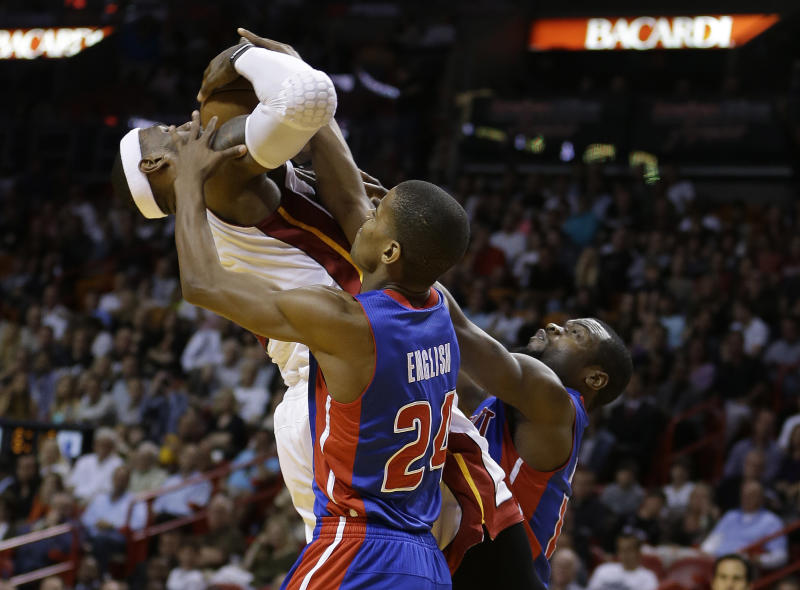 Miami Heat's LeBron James (6) is fouled by Detroit Pistons players Will Bynum (24) and Kim English (12) during the first half of a NBA basketball game in Miami, Friday, March 22, 2013. (AP Photo/J Pat Carter)