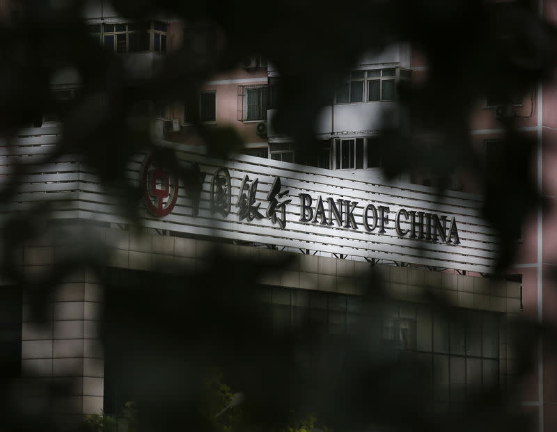Bank of China's logo is seen through trees at its branch office in Beijing