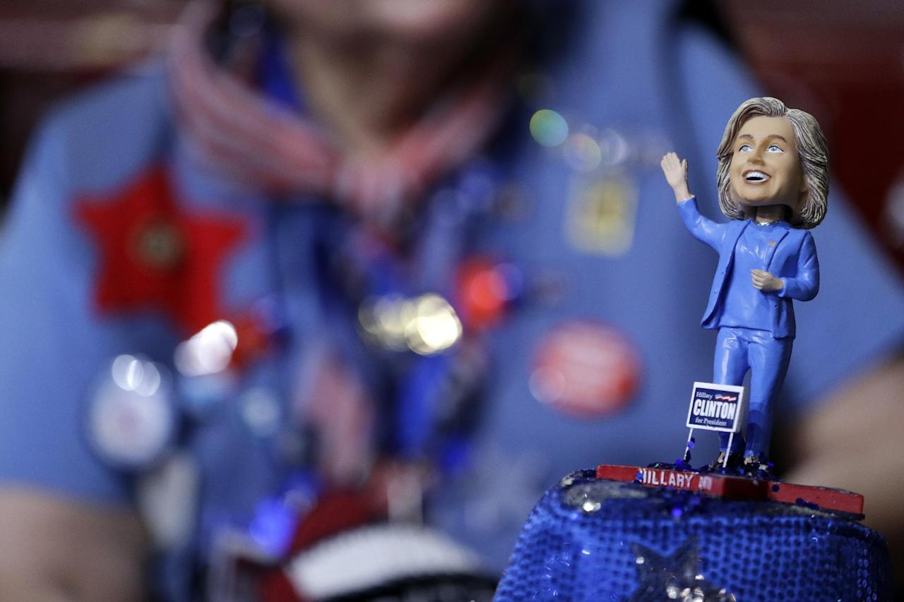 A delegate wears a hat with a bubble-head doll of Democratic Presidential candidate Sec. Hillary Clinton during the first day of the Democratic National Convention in Philadelphia , Monday, July 25, 2016. (AP Photo/John Locher)