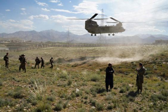A US military Chinook helicopter lands on a field outside the governor's palace during a visit by the commander of US and NATO forces in Afghanistan, in Maidan Shar, capital of Wardak province (AFP via Getty Images)
