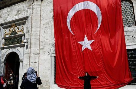 A woman poses in front of a huge Turkish flag in Istanbul