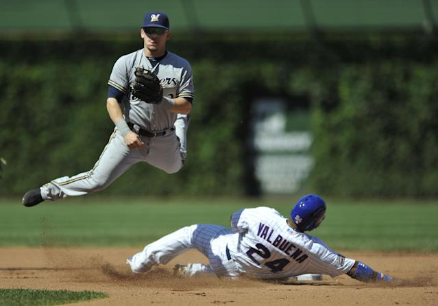 Milwaukee Brewers second baseman Scooter Gennett watches his throw to first base after forcing out Chicago Cubs' Luis Valbuena at second base during the second inning of a baseball game in Chicago, Monday, Sept. 1, 2014. (AP Photo/Paul Beaty)