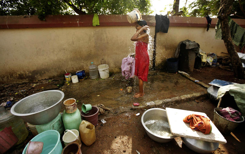A woman bathes using water collected from various areas on World Water Day at a slum in Bhubaneswar, India, Thursday, March 22, 2012. The U.N. estimates that more than one in six people worldwide do not have access to 20-50 liters (5-13 gallons) of safe freshwater a day to ensure their basic needs for drinking, cooking and cleaning. (AP Photo/Biswaranjan Rout)