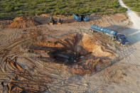 In this June 2021 photo provided by rancher Ashley Williams Watt, the Estes 24 well leaks on the Antina ranch near Crane, Texas. Chevron, which is responsible for the abandoned well, has been working to re-plug it. Buried under the sand, it became unplugged and started leaking produced water, a byproduct of oil production that is considered a toxic substance. The rancher's biggest worry is that it will get into her drinking water supply and the watershed, which flows into the nearby Pecos River. (Ashley Williams Watt via AP)