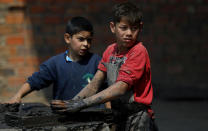 Mauri, 11, left, and Cesar, 13, work at a clay brick factory in Tobati, Paraguay, Friday, Sept. 4, 2020. The boys have been working at the factory, run by Mauri's family, since before schools stopped operating in March amid the COVID-19 pandemic. (AP Photo/Jorge Saenz)