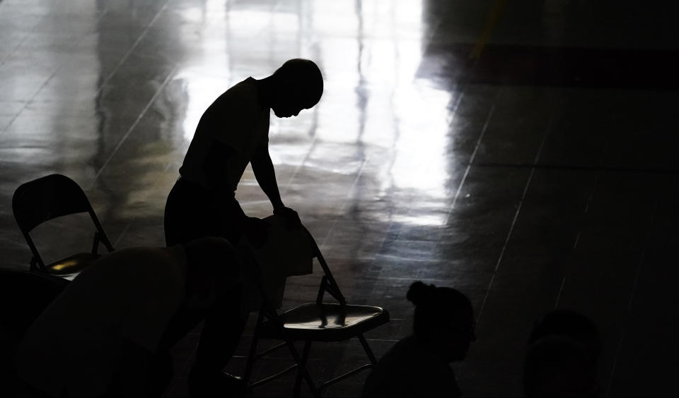 A man prays during Mass in the gymnasium at St. Joan of Arc Catholic Church in LaPlace, La., Sunday, Sept. 5, 2021, in the aftermath of Hurricane Ida. (AP Photo/Matt Slocum)