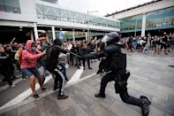 Protesters clash with police officers as they demonstrate at the airport, after a verdict in a trial over a banned independence referendum, in Barcelona